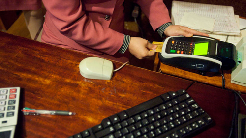 A woman swipes a North Korean debit card at the cash register of a hotel restaurant in Pyongyang, North Korea. A new culture of commerce has arisen, with China as its inspiration and source. The new consumerism is part of a campaign to build up the economy, and with it the image of new leader Kim Jong Un
