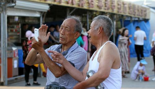 Hai người cao niên đang sử dụng điện thoại di động ở tỉnh Sơn Đông, tháng 5/2017. Ảnh: VCG