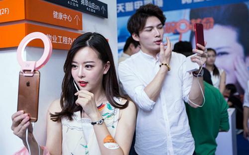 Một phụ nữ và một người đàn ông đang live stream tại một sự kiện thương mại ở Hàng Châu, Chiết Giang. Ảnh: China Daily