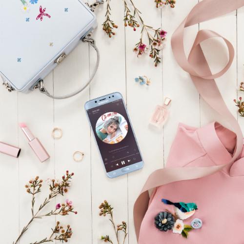 Túi xách trắng dễ kết hợp vớiáo dài, kích thước 18-20cm đựng vừa vặn chiếc smartphone Galaxy J7 Pro màu xanh ánh bạc.