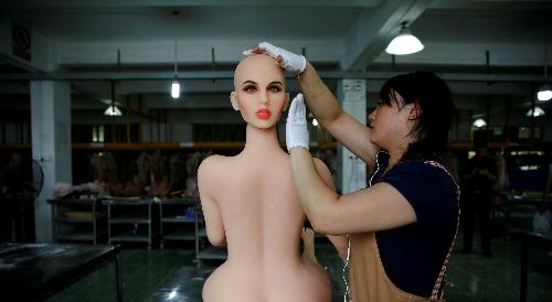Công nhân đang lắp đầu vào thân của búp bê. Ảnh: Reuters