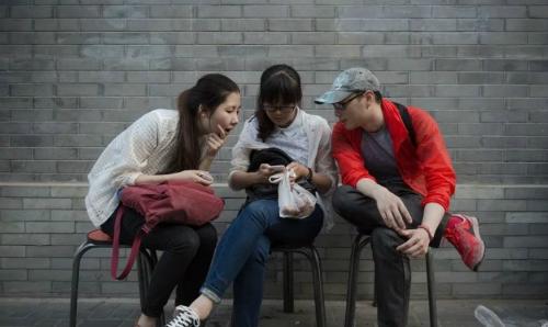 Một nhóm bạn trẻ đang ngồi xem điện thoại