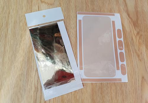 Miếng dán cho iPhone X màu trắng (bên phải) có màu trong suốt, trong khi cho bản màu xám đen có màu ánh kim.