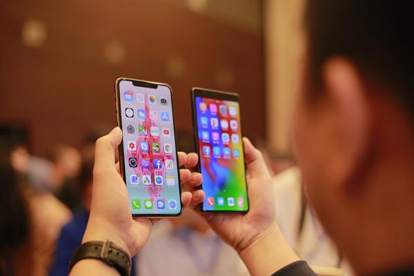 Một người so sánh mức độ tràn đáy của Bphone 3 so với iPhone X. Viền đáy của Bphone mỏng hơn.