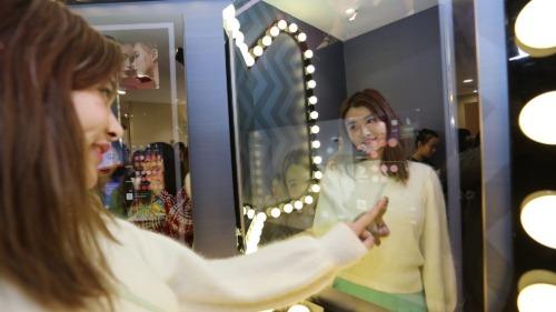 Một phụ nữ đang thử đồ trước gương ma thuật. Ảnh: Alizila