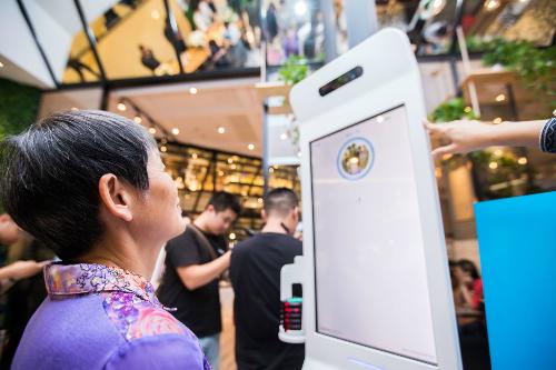 Một phụ nữ đang trả tiền hóa đơn bữa ăn bằng cách cười trước camera.