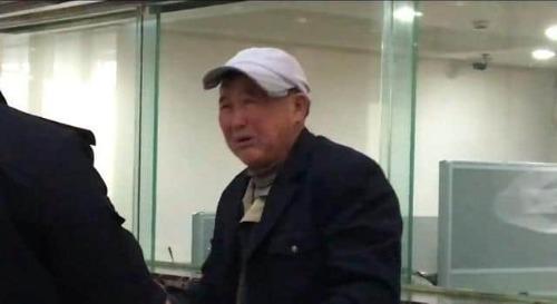 Người đàn ông lớn tuổi khóc tại nhà ga vì không biết mua vé tàu trực tuyến. Ảnh: Sina