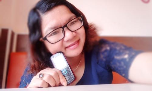 Chị Lệ Thuỷ cùng chiếc điện thoại Nokia đầu tiên.