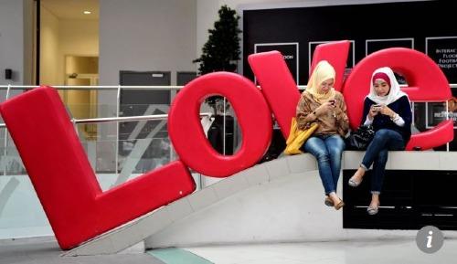 Hai người phụ nữ đang vào mạng xã hội bằng điện thoại di động ở Jakarta.