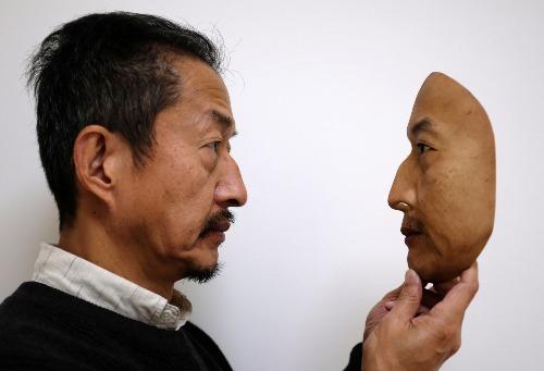 Kitagawa và chiếc mặt nạ sao chép khuôn mặt của chính mình. Ảnh: Reuters