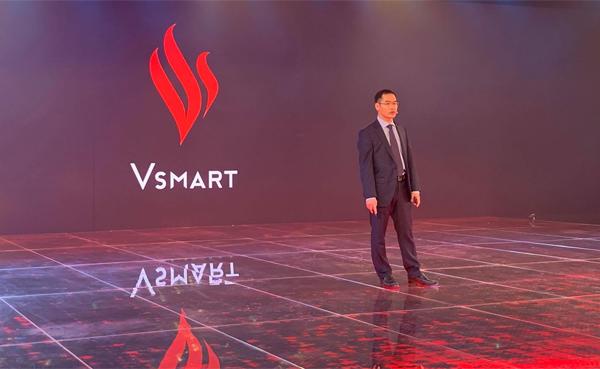 Ông Trung đứng cạnh logo của VinSmart với ý nghĩa hai ánh lửa đầu tiên là của Vingroup vàánh lửa thứ ba chính là VinSmart thể hiện khát khao thành côngcủa công ty.