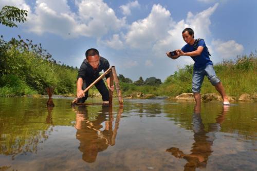 Một nông dân đang livestream việc câu tôm sông lên mạng xã hội ở tỉnh Hồ Nam. Ảnh ChinaDaily