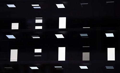 1.000 chiếc smartphone đặt trên giá ngang, phản chiếu ánh sáng vào mặt kính tạo hiệu ứng thị giác cho kiến trúc tòa nhà.