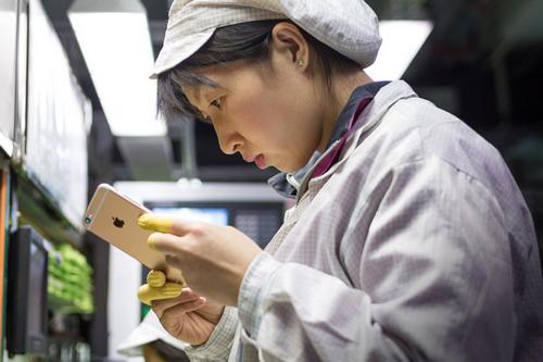 Một công nhân lắp ráp iPhone trong nhà máy Foxconn. Ảnh: Sina.
