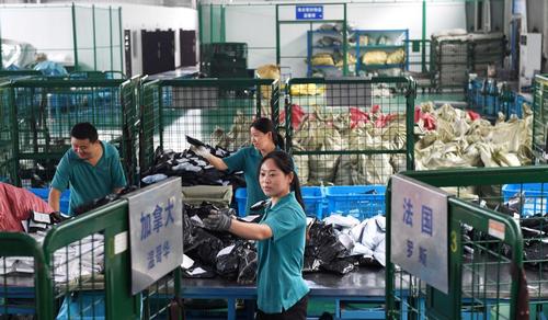 Các công nhân sắp xếp hàng hóa trong ngày lễ độc thân ở Hợp Phì, An Huy (Trung Quốc). Ảnh: Reuters.