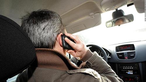 Việc vừa lái xe vừa dùng điện thoại được xem là hành động nguy hiểm khi tham gia giao thông. Ảnh: CNN.