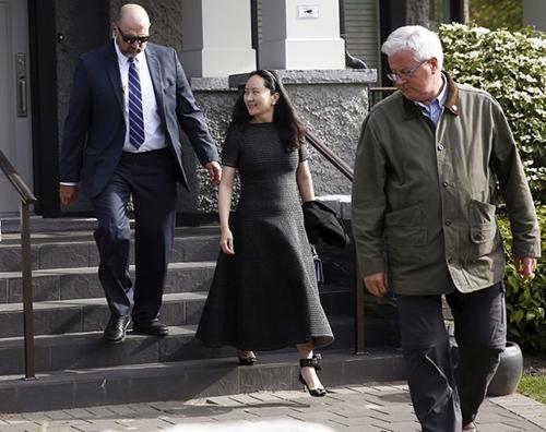Mạnh Vãn Chu bị quản thúc bởi các nhân viên an ninh và thiết bị đeo ở chân. Ảnh: Reuters.