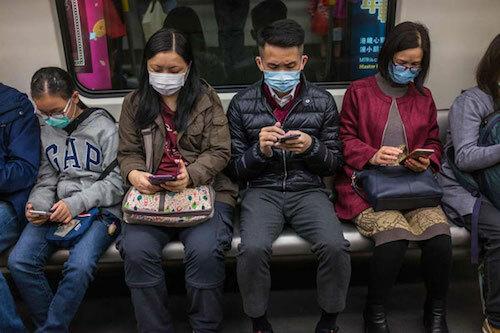 Người dùng smartphone đeo khẩu trangtrên một chuyến tàu ở Hong Kong. Ảnh: AFP.