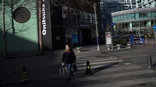 Một người phụ nữ đeo khẩu trang đi mua sắm tại một trung tâm thương mại ở Bắc Kinh ngày 17/2. Ảnh: Reuters.