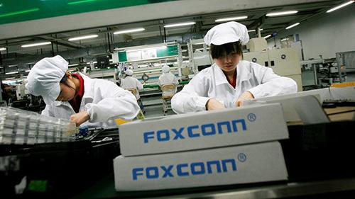 Công nhân lắp ráp thiết bị điện tử tại nhà máy Foxconn Quảng Châu (Trung Quốc). Ảnh: Reuters.