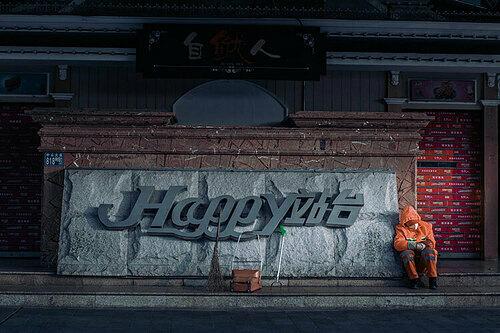 Một người lao công đeo mặt nạ ngồi nghỉ trước trung tâm thương mại từng rất đông đúc ở Vũ Hán. Bức ảnh được chụp bào 4h30 chiều ngày 27/1. Ảnh; Xie Dan.