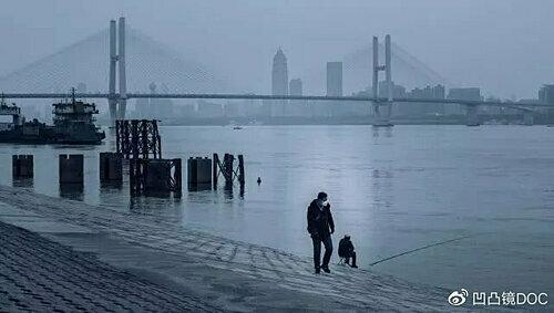 Người đàn ông ngồi câu cá bên bờ sông, khung cảnh ảm đạm trái ngược hoàn toàn với nhịp sống sôi động hàng ngày nơi đây. Ảnh: Xie Dan.