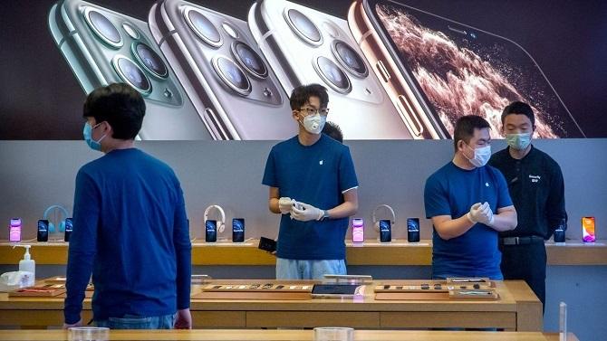 Các nhân viên Apple Store ở Bắc Kinh phải đeo khẩu trang trong ngày mở cửa trở lại. Ảnh: WSJ.