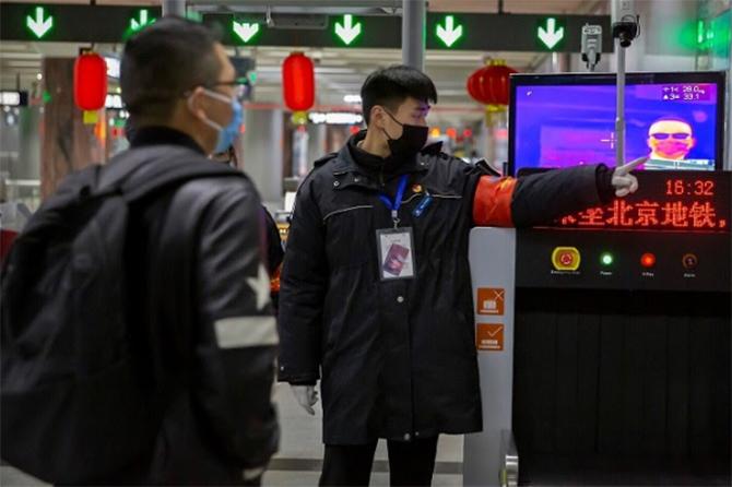 Nhân viên an ninh tại một nhà ga theo dõi hành khách qua hệ thống đo thân nhiệt. Ảnh: AP