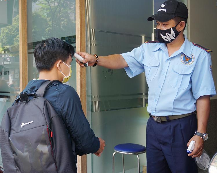 Nhân viên đo thân nhiệt và xịt sát khuẩn cho khách trước khi vào trung tâm bảo hành. Ảnh: Hiền Trang.