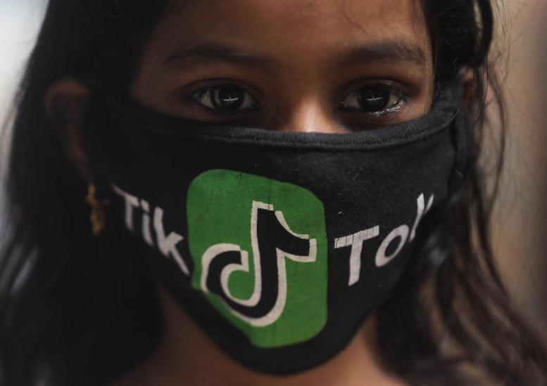 Một cô gái đeo khẩu trang có logo TikTok tại Mumbai (Ấn Độ). Ảnh: Reuters.