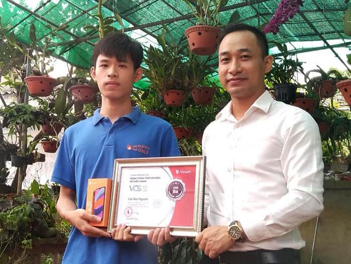Cao Bảo Nguyên (bên trái) nhận Giấy chứng nhận cho người đạt giải trong chương trình Trải nghiệm hệ điều hành của Vsmart, ngày 21/7, tại nhà cậu ở Thái Bình.