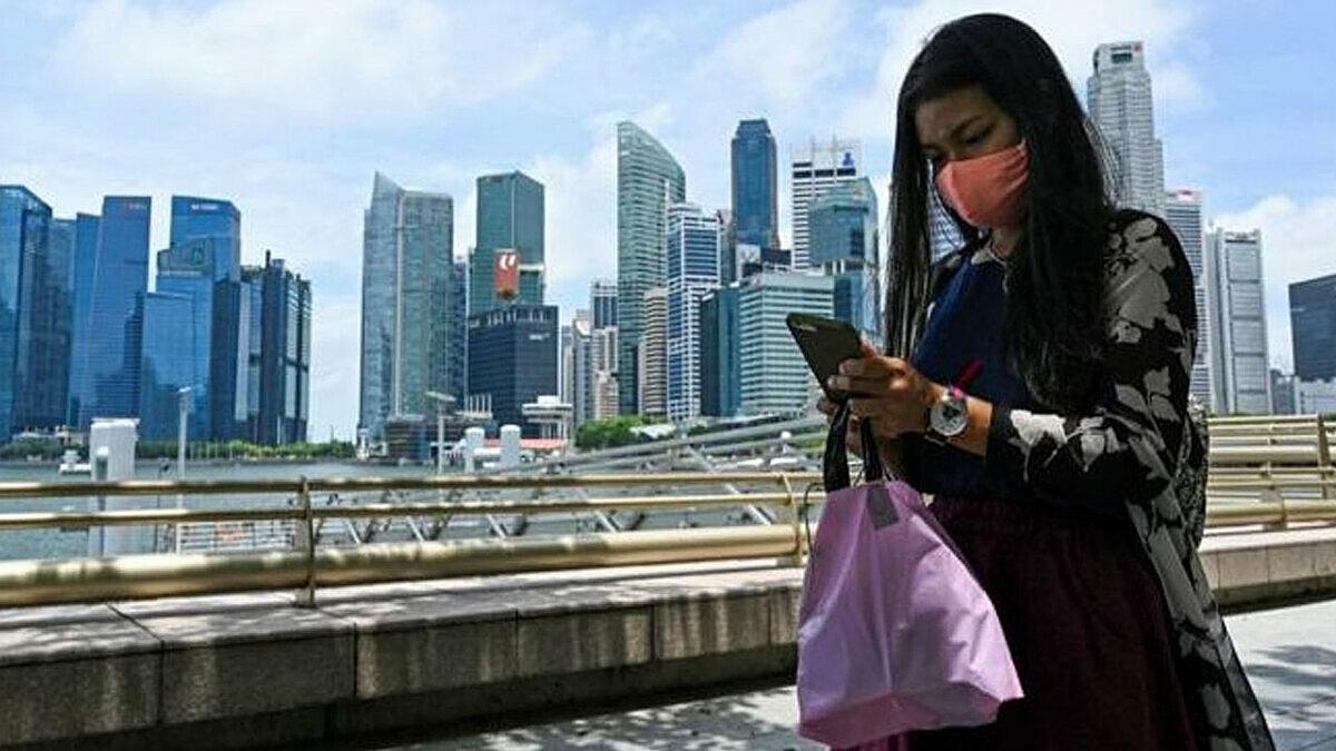 Một người phụ nữ Singapore đang chăm chú trước màn hình điện thoại. Ảnh: BBC.
