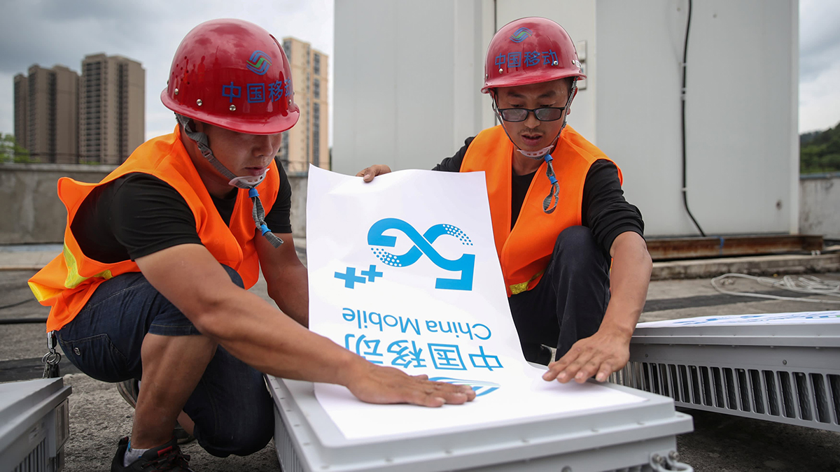 Hai công nhân đang lắp đặt một trạm gốc 5G tại tỉnh Quý Châu. Ảnh: Reuters.