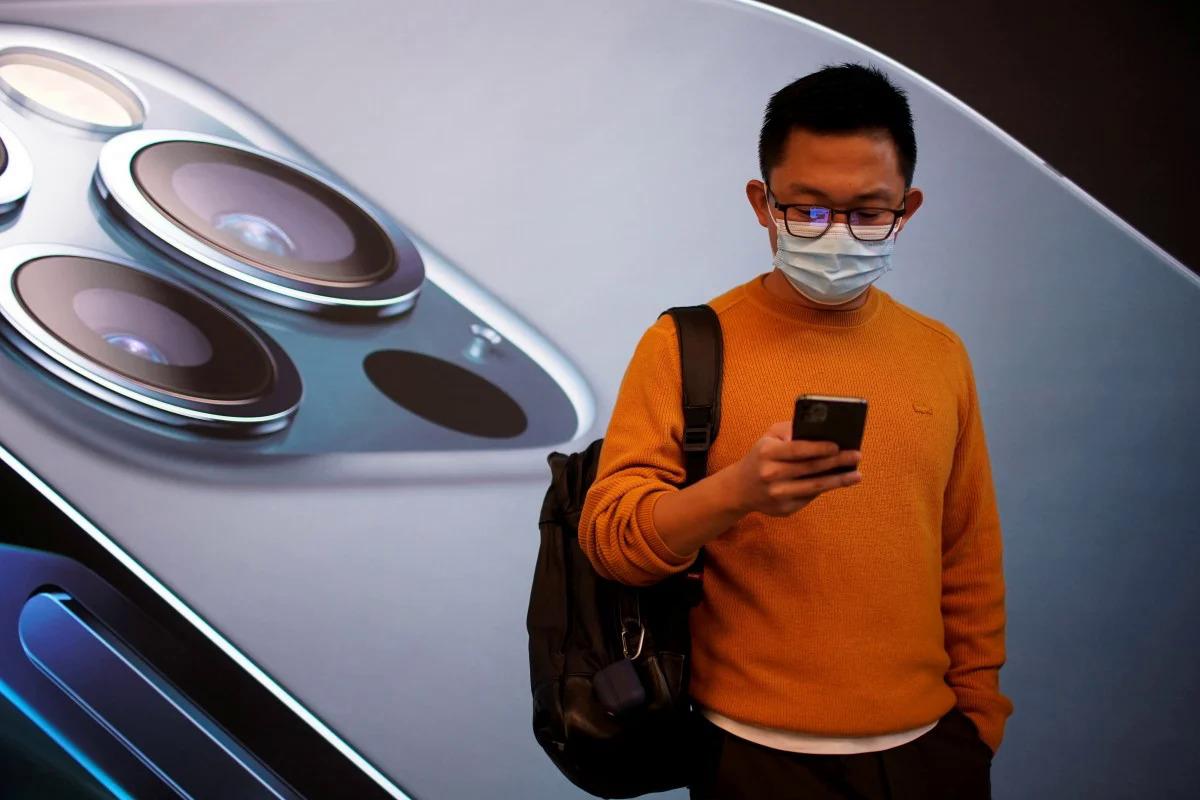 Một người đàn ông đứng trước Apple Store tại Thượng Hải (Trung Quốc). Ảnh: Reuters.