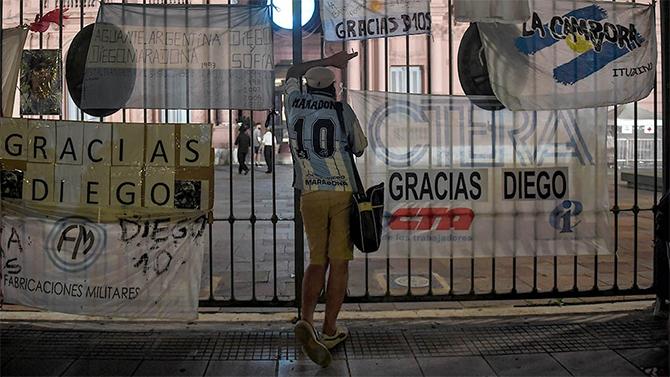 Người hâm mộ đứng bên cạnh hàng rào gắn các biểu ngữ tưởng nhớ Maradona. Ảnh: Telam