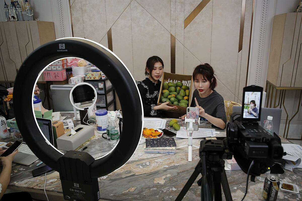 Blogger Zhang Mofan (phải) giới thiệu xoài tươi cho khách hàng và người hâm mộ của cô thông qua Live-stream. Ảnh: AP