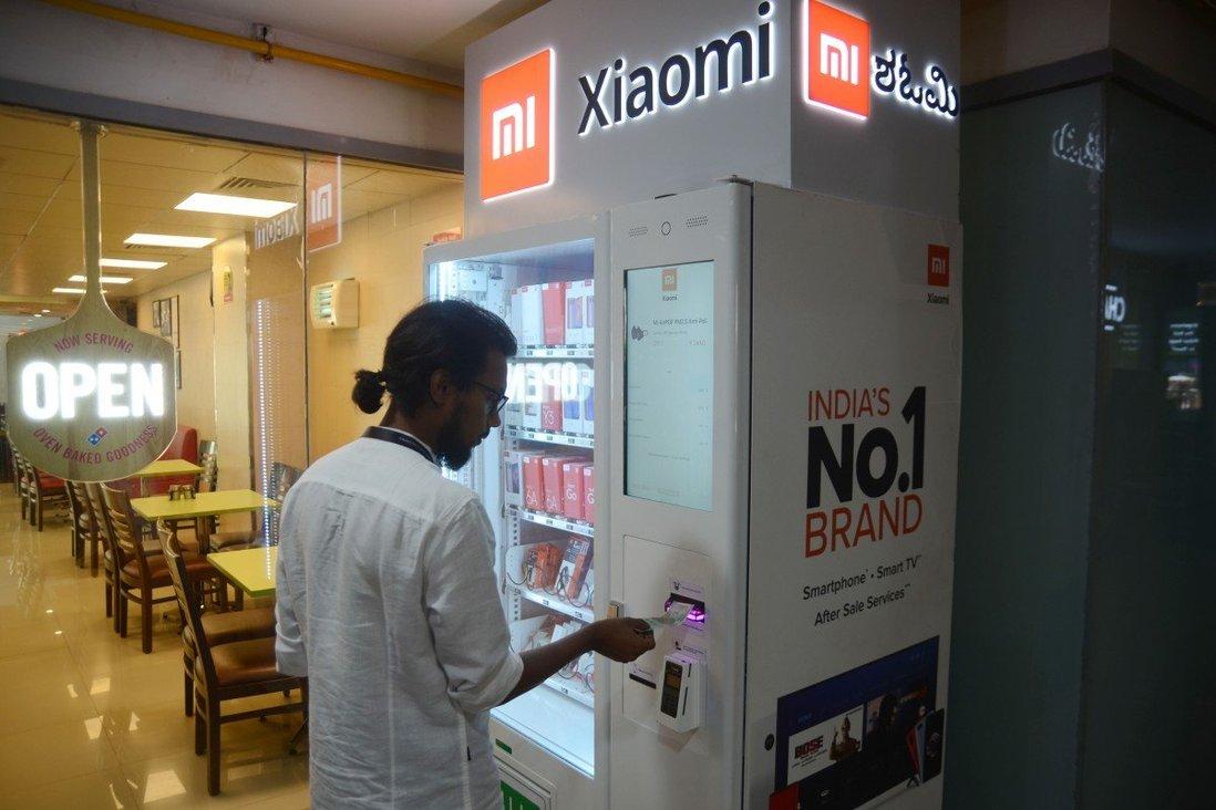 Một người đàn ông mua smartphone qua máy bán hàng tự động tại Ấn Độ. Ảnh: Xinhua.