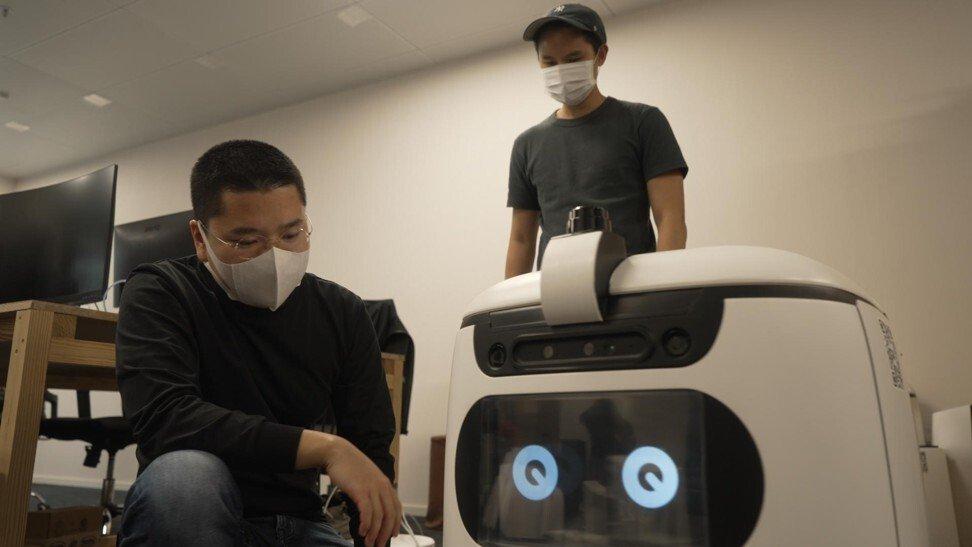 Victor Lee (trái) bên cạnh robot tự động do công ty anh phát triển. Ảnh: SCMP.
