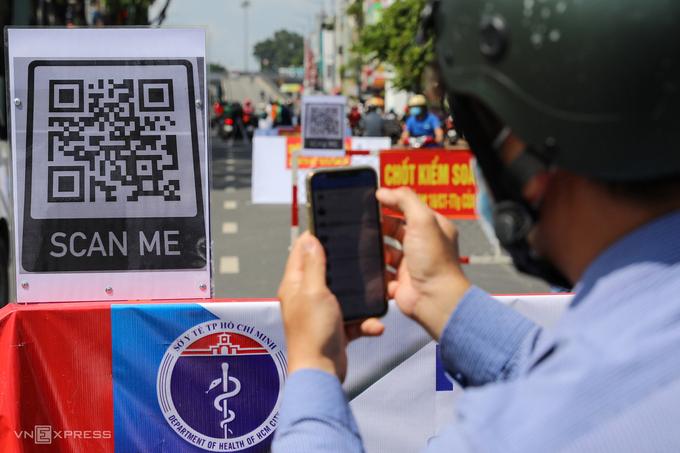 Người dân quét mã QR Code khai báo y tế điện tử tại một chốt kiểm dịch Covid-19. Ảnh: Quỳnh Trần.