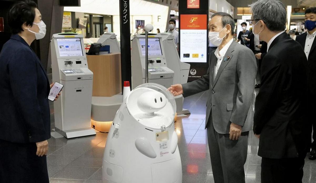 Thủ tướng Nhật Bản Yoshihide Suga bên cạnh một robot ở sân bay Haneda. Ảnh: Kyodo.