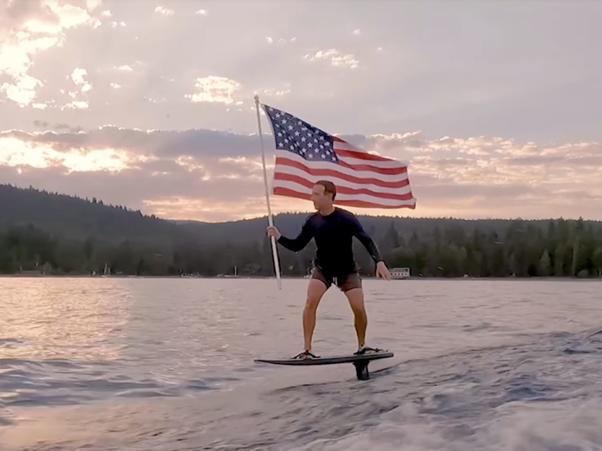 Mark Zuckerberg lướt ván cánh ngầm Hydrofoil tay cầmi cờ Mỹ. Ảnh: Facebook.
