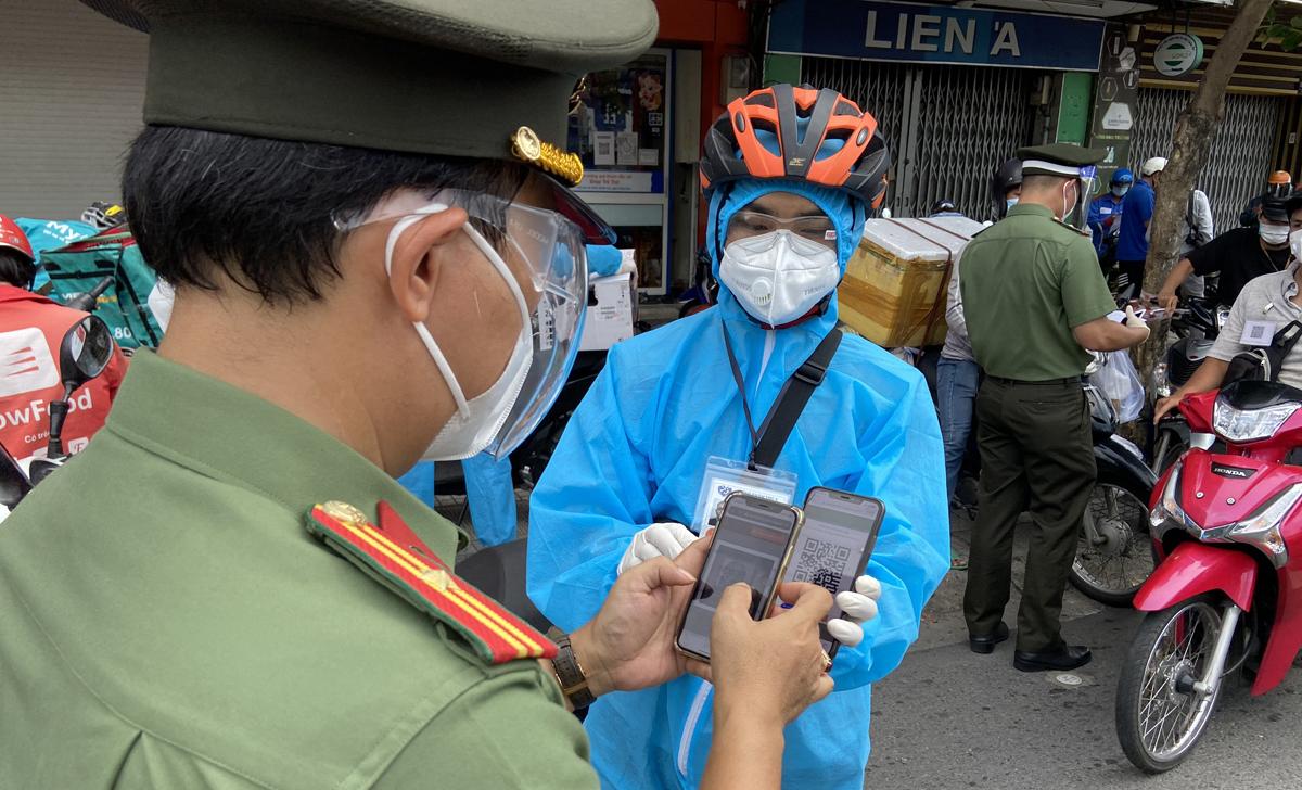 Người dân tại TP HCM khai báo di chuyển và xuất trình mã QR để cơ quan chức năng kiểm tra hôm 14/8. Ảnh: Hạ Giang