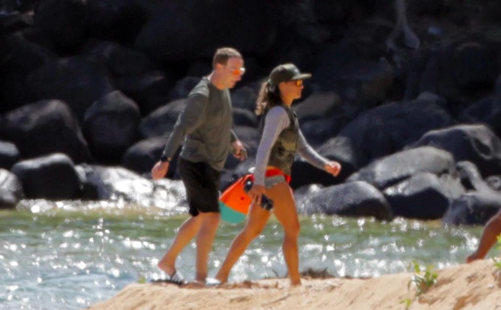 Mark Zuckerberg đi dạo cùng một người phụ nữ trên bãi biển Kauai hôm 29/8. Ảnh: Mega