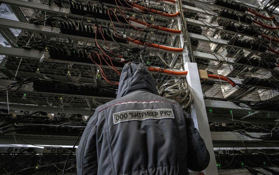 Một nhân viên đang vận hành trung tâm dữ liệu của khu khai thác Bitcoin ở Irkutsk, Nga tháng 3/2021. Ảnh: Reuters